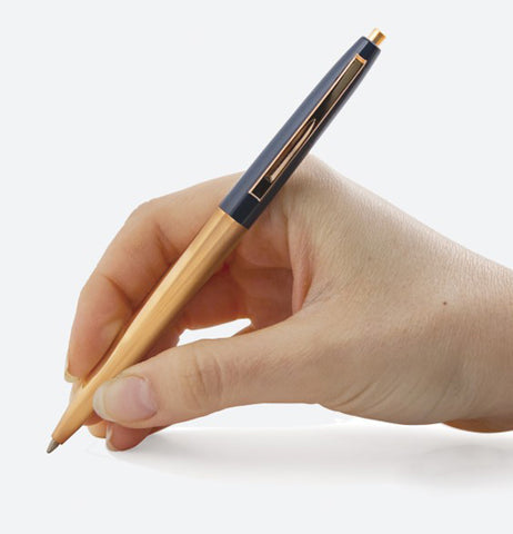 A person's hand is shown writing with the blue and copper pen.