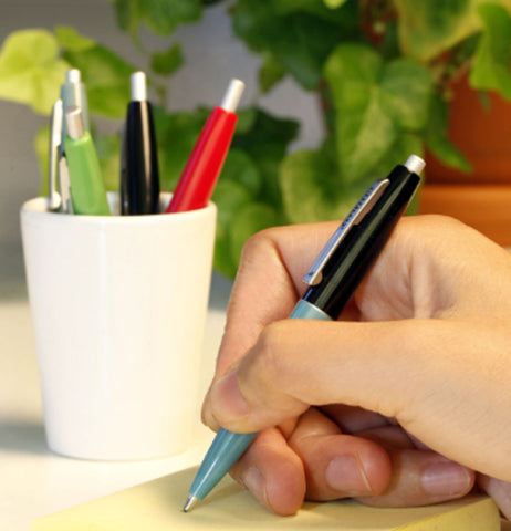 A person's hand is shown writing on some paper with one of the pens. Three more pens are seen inside a cup.