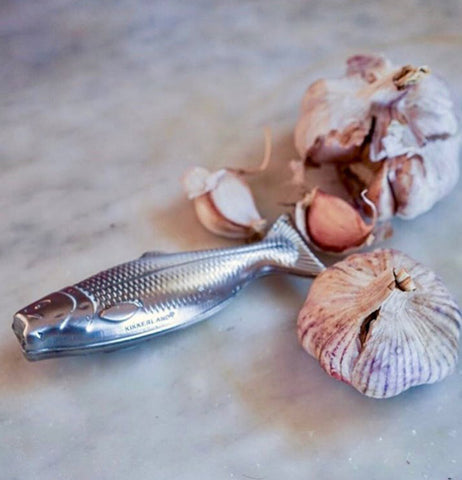"The Magic Soap ""Fish"" sits on a wooden table with two cloves of garlic."