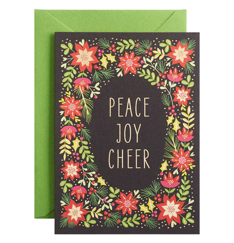 "This black Christmas card features a collage of green leafed plants with red flowers taking up most of its front. In the middle of the design are the words, ""Peace, Joy, Cheer"" in greenish white lettering against a black background surrounded by the plant collage. Underneath the card is its bright green paper envelope."