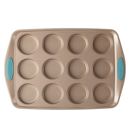 "The 12 Cup ""Blue"" Muffin Pan is on display on a white background. The pan is a bronze color that has 12 cup holes with blue handles."