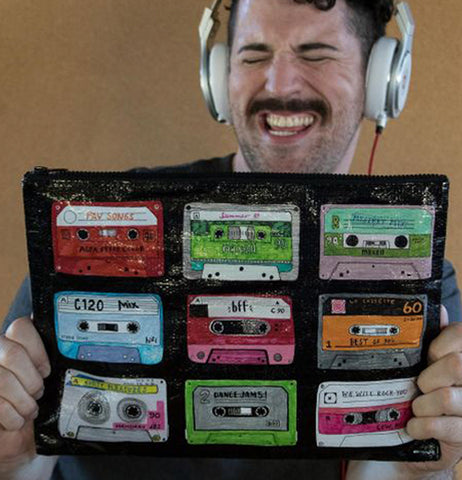 A mustached man with silver headphones holds the black pouch with the different colored tapes.