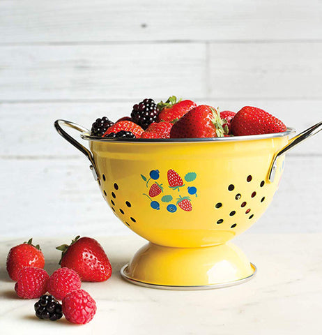 "The Yellow ""Berry Patch"" colander holds a large amount of strawberries and blackberries."