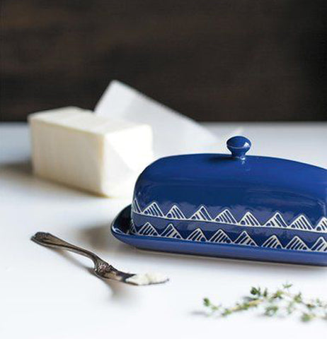 A Blue butter dish with a design of two rows of mountains running along the bottom.with a cube of butter and a butter knife.