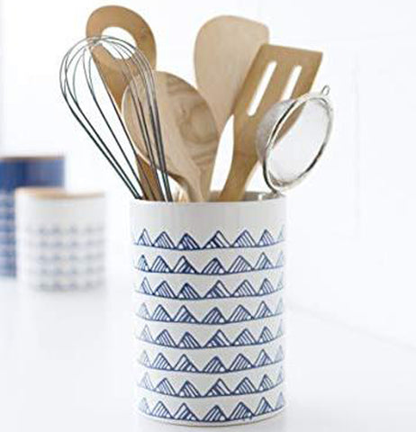 Some wooden and metal cooking utensils are shown inside the white utensil crock with the blue mountain top designs covering it.