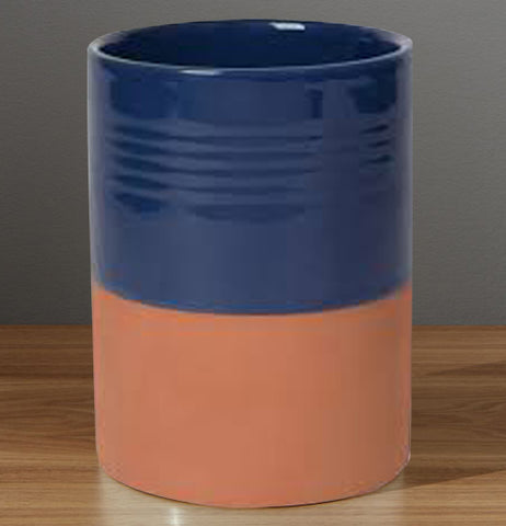 Navy blue glazed and brownish-red terracotta kitchen utensil crock on wood.
