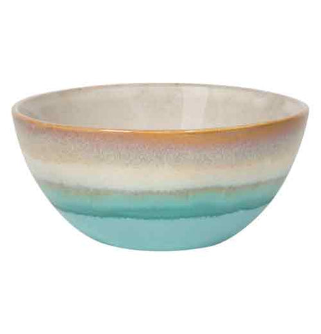 A ceramic bowl that has some browns and some green coloring on it.