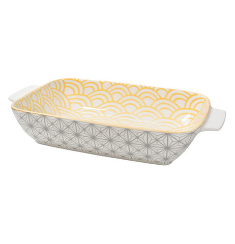 Close up of a yellow baking dish with a sunstone pattern on the interior, and a grey geometric pattern on the exterior.