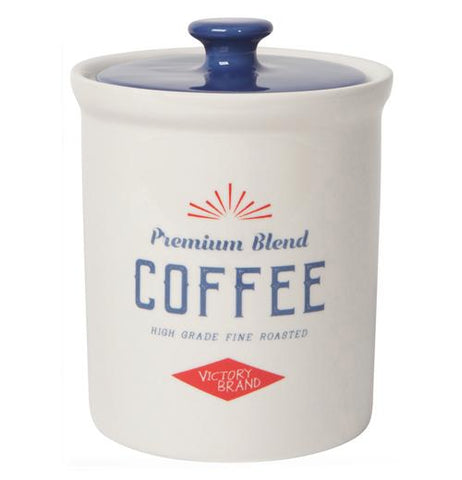 "The white Dry Goods ""Coffee"" Vintage Canister has the words,""Sunrise Mills Co. Fine Granulated Coffee Quality Product"", in red and blue letters with a blue lid on top."