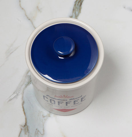 "The blue lid on the Dry Goods ""Coffee"" Vintage Canister is shown sitting on a white marble table."