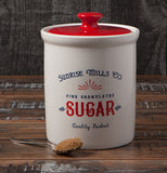 "The Day Goods Vintage ""Sugar"" Canister sitting on the brown wooden table with the teaspoon of coffee grounds close to it."
