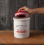 "The hand opening the lid of the Dry Goods ""Sugar"" Vintage Canister."