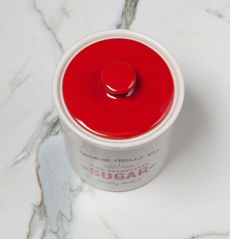 "The showing of the red lid on the Dry Goods ""Sugar"" Vintage Canister sitting on the white marble table."