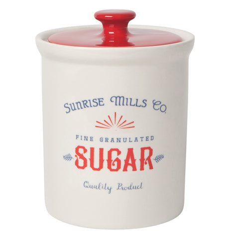 "The white Dry Goods ""Sugar"" Vintage Canister has the words,""Sunrise Mills Co. Fine Granulated Sugar Quality Product"", in red and blue letters with the red lid on top."