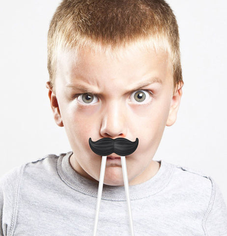 A little boy has the moustache chopsticks sitting on his upper lip.