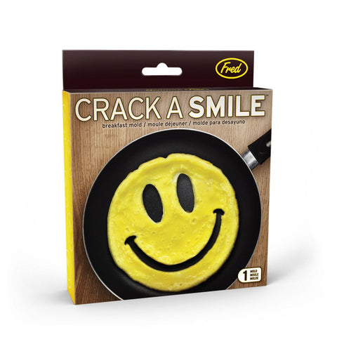 """Crack A Smile"" pancake and egg mold in its box with scrambled eggs shaped like a smiling face in a black pan on a brown background."