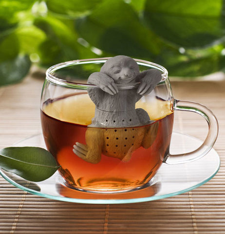 The gray smiling sloth is hanging from the rim of a clear glass filled with tea that's sitting the table.