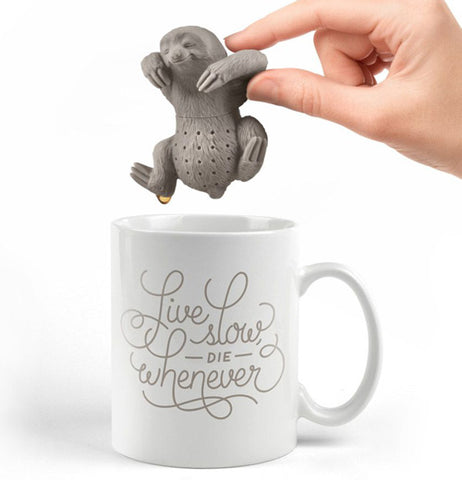 A hand taking out a gray smiling sloth from the cup of tea.