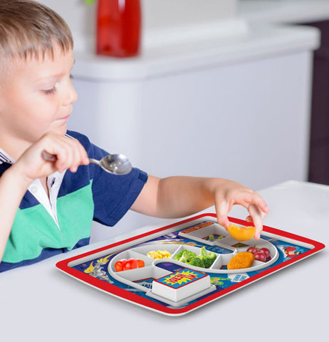 The child eating food on a Supper Hero Dinner Plate on a table.