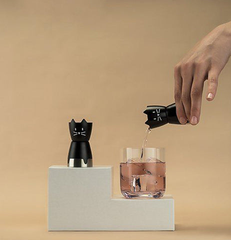 A person's hand is shown pouring some liquor from the cat shaped shot glass into a larger glass.