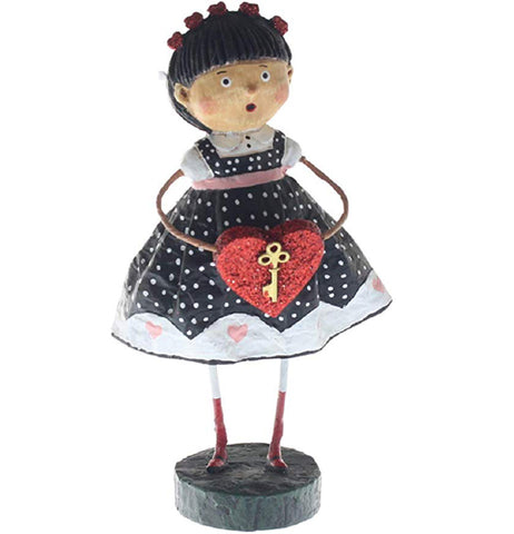 A resin figure of an olive-skinned girl. She is wearing a black dress with white polka dots, pastel pink hearts across the bottom, and a pastel pink ribbon across her chest. She is holding a red heart with a gold-painted key on it. She wears red socks and white leggings. She is standing on a black base.