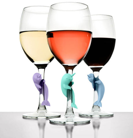 Three of the Narwhal Social Climbers wine markers on the stems of the three wine glasses.