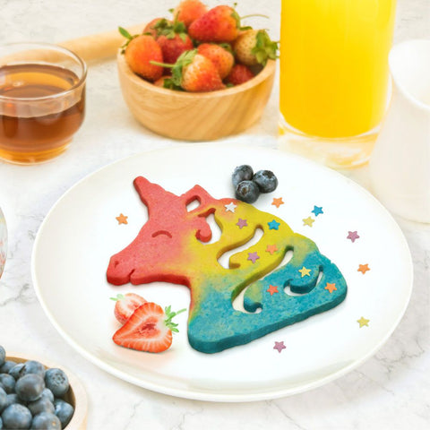 Red, yellow, and blue colored unicorn head shaped pancake covered with star sprinkles on round white plate with blueberries and sliced strawberries laying next to them. A bowl of blueberries is off to the lower left and on top is a clear cup of syrup, a bowl of strawberries, and a glass of orange juice.