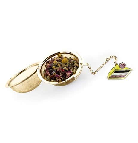 Open gold tea infuser with tea leaves inside with a charm attached shaped like a slice of birthday cake.