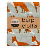 "This large burping cloth features a design of red foxes against a gray background. Wrapped around the cloth is its cardboard packaging with the black and white logo, ""Milkbarn"" and the words, ""Burp cloths"" in black lettering."