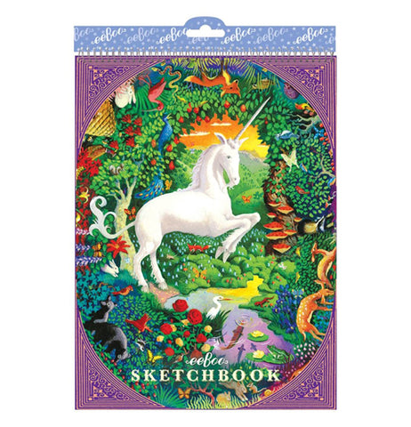 "This sketchbook has a picture of a white unicorn in the middle of a green forest surrounded by trees, red mushrooms, and green leaves. The words, ""eeboo Sketchbook"" are shown at the bottom in white lettering."