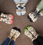 "A pair of feet wearing a ""Makin' Waves"" Ankle Socks along with other four other pairs of feet wearing other decorative socks standing in a circle."