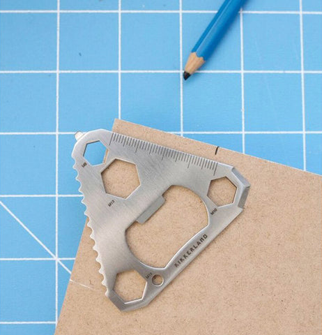 The triangular multi-tool is shown lying on some cardboard on some blue and white grid paper next to a blue pencil.