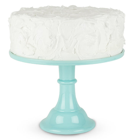 A cake is shown sitting on the mint-colored melamine cake stand.