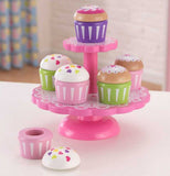 pink cupcake stand with various cupcakes sitting on a counter