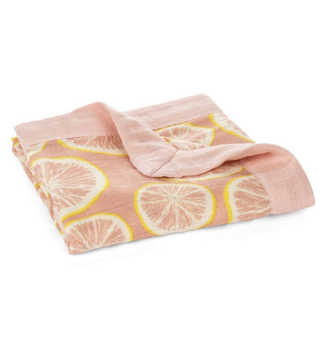 Shown here is a folded peach colored blanket with pink and yellow grapefruits.