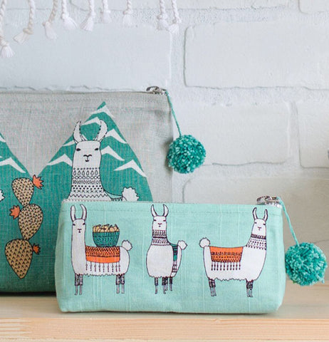 A llamarama cosmetic bag with a llamarama purse sitting on a table against a white brick wall.
