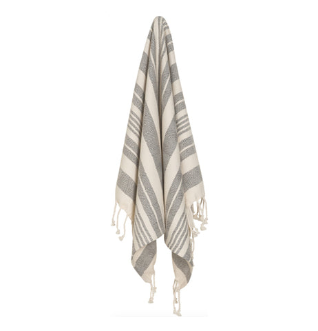 Gray and white striped hand towel with white twists on the end hanging up on a white background.