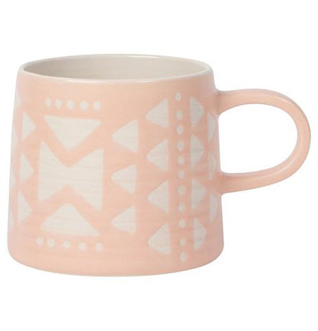 A Pink Mug with white triangles and circles with a pink handle on a white background.