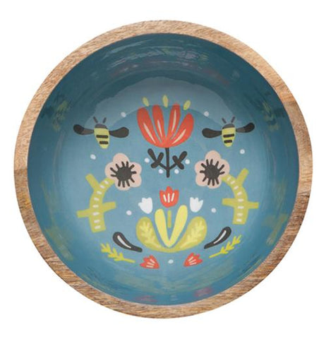 This wooden bowl has a blue bottom interior with a design of two bees pollinating a red flower. Two yellow flowers stand on either side of the red flower.