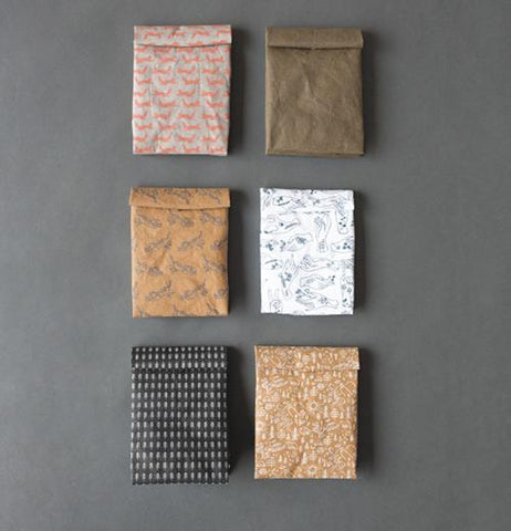 Overview of six different closed lunch bags laying down on a gray background.