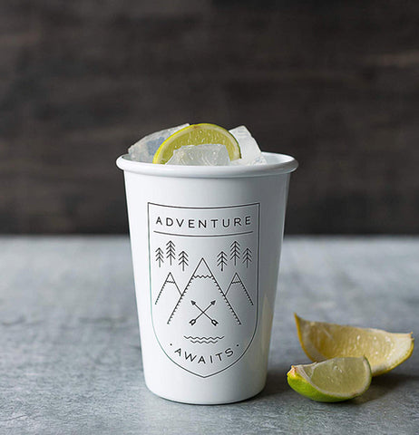 "The ""Adventure Awaits"" Tumbler is filled with a drink and has a lemon and a lime on the side."