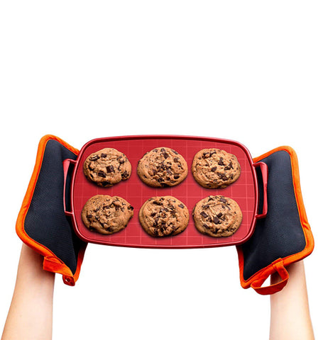 From a top view, there is a pair of hands holding the baking sheet by the side handles with baking mitts and six cookies that are already baked.