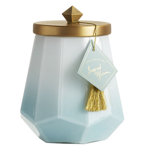 The candle is in a glass container that fades from white at the top to blue at the bottom and a gold top with a gold tassel hanging from the lid.