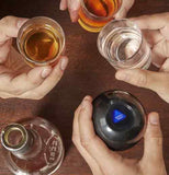 "Hands holding black round ball drinking game with words that read ""Buddy Shot"" with 3 other hands holding filled shot glasses over a brown table."