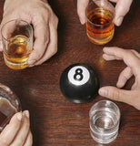Round black and white 8 ball drinking game with black 8 on brown table. Three hands are holding full shot glasses with another hand reaching for the 8 ball a full glass sits next to the game.
