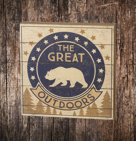"The box with a navy blue and cream colored circular bear symbol with the words, ""The Great Outdoors"" In navy blue and cream colored lettering and pine trees below the words sits on a wooden surface."
