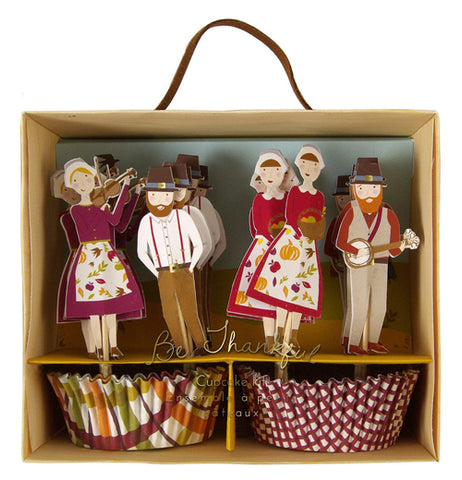 A box of Thanksgiving pilgrim figures with some musical instruments is shown. Below the figures are cupcake holders, one of which has a stripe pattern of red, orange, and green. The other has a red and white checkered pattern .