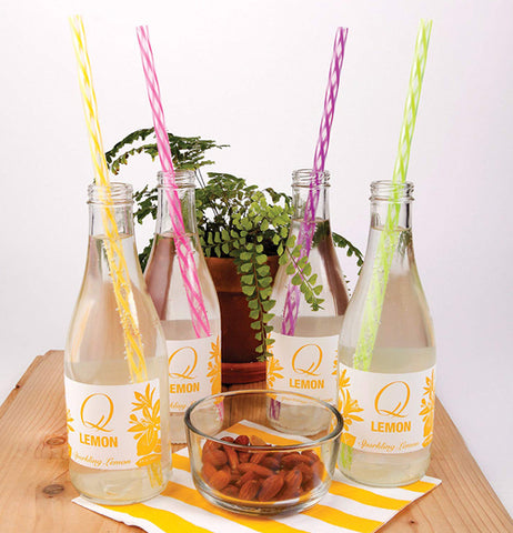 Four different colored reusable straws, one yellow, another pink, another purple, and the last lime green, being used in four sparkling water bottles on a table with nuts and a plant in the background