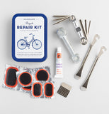 The bicycle repair kit lies next to the items in the kit such as patches, wrenches, buffer, metal tire levers, glue, and an Allen wrench set.