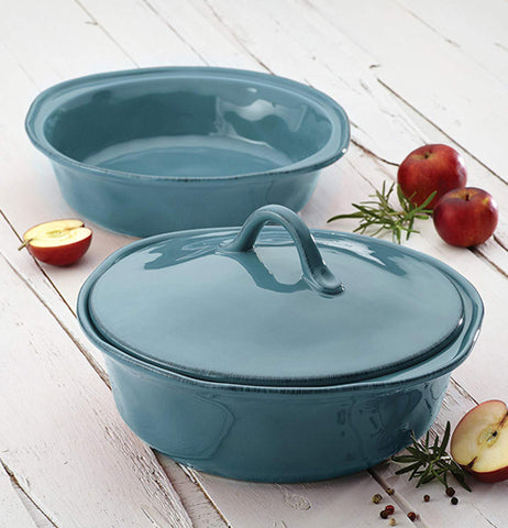 "1.5 ""Agave Blue"" casserole dish without lid and 2 quart ""Agave Blue"" casserole dish with lid on white wood floor with apples next to them."
